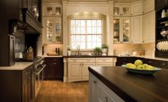 If the floor in this kitchen had been stained a dark, matching brown tone, all those beautiful cabinets and countertops would get lost against it. The golden tone of the floor serves to create contrast and adds a third color layer. This kitchen also throws an unexpected curve: The sink base cabinets become their own element, painted white in a run of dark stained cabinetry.