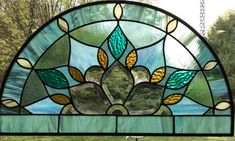 This lovely Half round arched window is reminiscent of peacocks in colors and design. It Has a beautiful bevel cluster surrounded in colors of various teal, sea-green, turquoise, and Amber accents. It is a half round hanging stained glass window panel with pewter patina. This is a beautiful panel and unique design. Measures 21.5x12.5  I can change colors and size. Just request this made in a custom size. Includes hanging chain