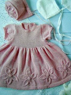 pink dress w/ knit floral detail. also, a bonnet.