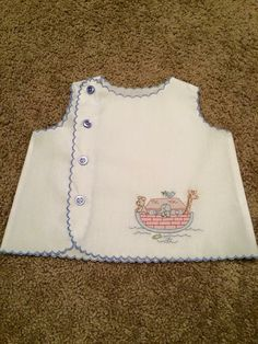 This vintage inspired white broadcloth baby boy diaper shirt features a shadow embroidered Noahs Ark on the front and machine scalloping on the