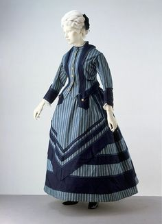 A jaunty, sensible woman's outfit of the early 1870s designed for boating or seaside walking. A hemline just at the ankle indicates a garment intended for walking outdoors. The style of the dress has been inspired by the colours and stripes of sailors' uniforms. It is made of cotton, so it is easily washed and dried. Despite its practical use, the ensemble still incorporates the details of fashionable dress, with an overskirt in front and a bustle worn underneath at the back.