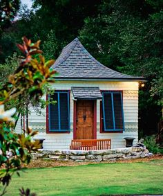 This tiny backyard cottage was once a little schoolhouse! The owners wanted to preserve the great details, like the flared roof. They jacked up the house and made it level, replaced shingles, repaired the original windows, and installed Bermuda shutters for extra charm.