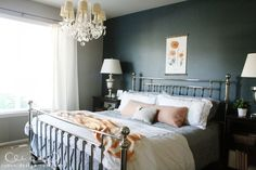 Love the dramatic dark wall with bright bedding and orange accents, via @emily
