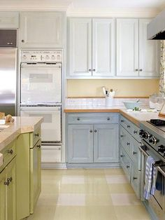 Color Blocking. Using two or three colors in large blocks in the kitchen makes a large space feel less intimidating and gives it a less formal, unfitted look. Dark colors appear heavy, so use them on the base cabinets and island and save the light tones for upper cabinets. Here, blue on the perimeter cabinets complement butter-yellow walls, and bright yellow-green makes the island a focal point.