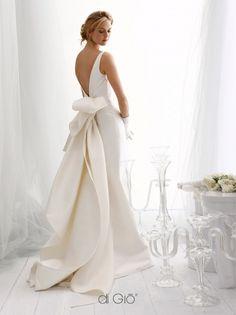Abito Haute Couture classico in mikado con linee a sirena, profonda scollatura a V dietro con grande strascico e fiocco.