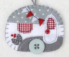 Vintage caravan trailer ornament, handmade from felt and decorated with fabric scraps. With tiny felt bunting and buttons for the wheel and door knob. Colors are grey and white with red details. With                                                                                                                                                      More