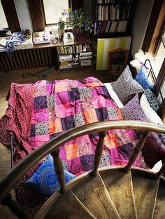 O patchwork da colcha enfatiza a beleza do quarto.