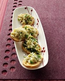 Artichoke-Parmesan Crostini  8 slices (1/4 inch thick) baguette  2 tablespoons olive oil  Coarse salt and ground pepper  1 jar (6 1/2 ounces) marinated artichoke hearts, drained, rinsed, and patted dry  1/4 cup shredded Parmesan cheese, plus more for garnish (optional)  1 tablespoon chopped fresh parsley