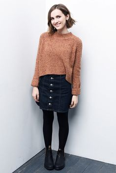 Maude Apatow wears a cropped mock-neck sweater, button-front denim skirt, tights, and Chelsea boots