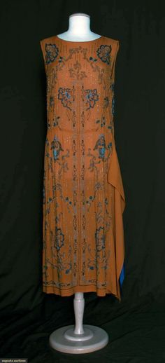 Rust silk crepe w/ fanciful flowers beaded in shades of blue, 2 hip to hem panels on left side in rust crepe & blue silk.  augusta-auctions.com