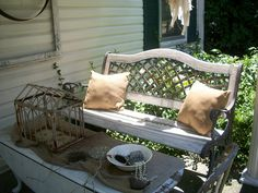 Porch with rusty cage and flower frogs on a burlap runner.