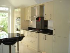 Larger extension fitted kitchen - gloss cream slab doors and absolute black granite worktops - Hertford, Herts - by Peter Hamilton Kitchens
