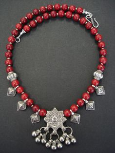 Coral and Silver Star Necklace Opulent necklace with rich dark red dyed coral 8mm beads and a wonderful old central silver star and flower pendant found in the Grand Bazaar Turkey with six old silver drop pendants from India and 2 old silver beads from Central Asia. Finished with 9.25 silver beads and clasp.