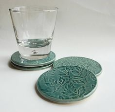 Set of four leaf textured ceramic coasters.   This set of coasters have a wonderful delicate leaf pattern covering the surface. They are made from high fired clay and are perfect for hot or cold drinks. There are four clear rubber feet on the underside of each coaster to stop them from slipping and marking any surfaces which they stand on.  Glazed, high fired earthenware ceramic.These coasters measure approx 9.5cm in diameter.