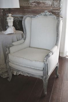 Sillón  francés  de alas de madera tallada y plateada con tapizado de lino Siglo  19