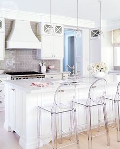 A backsplash of greyish taupe ceramic subway tiles offers a soft hit of colour in this all-white kitchen. LIKE? Tour the entire Victorian home, visit styleathome.com/homes/interiors {Photo: @staceyvanberkel | Design: Margie Doyle White}