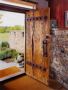 Two inch thick oak barn threshing floor boards and custom hand forged hardware become stout front entrance door. Original red barn siding reused as interior wall treatment. Love thick wooden doors and stone! Cool Doors, The Doors, Windows And Doors, Panel Doors, Front Door Entrance, Front Entrances, Entry Doors, Sliding Doors, House Entrance