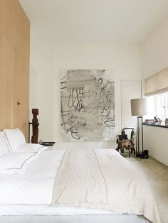 The master bedroom is a serene conjuring of sublimely relaxed hues broken up with a bit of rock 'n' roll edge courtesy of a painting by Christopher Wool.