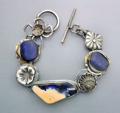 Sterling silver with an boulder opal and two tribal cut old lapis pieces. Included is a tiny ammonite fossil and silver elements. This bracelet is chunky.   Temi Kucinski