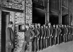 Pay day at Butlers Wharf, London. A line of workmen collect their wages from a hatch, while a security guard looks on. Photographer unknown, C1910.