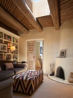 This cozy sitting room off the master suite features classic Southwestern touches, such as a kiva fireplace, hand-plastered walls, and carved wooden doors. A stunning skylight brightens up the space during the day.