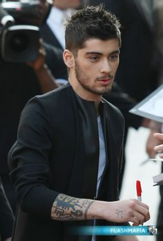 Zayn Malik Stops for Autograph during World Premiere of One Direction:This Is Us on Flashmafia...(Check out more pictures and upload your own Zayn Malik pix to FlashMafia.com) #OneDirection