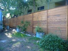 Stained cedar fence constructed with finish boards, top-cap & trim
