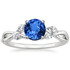 Wispy vines of precious metal entwine toward lustrous marquise diamond buds in this nature-inspired trellis ring (0.13 total carat weight).    This ring is set with a stunning round blue 6mm Ceylon sapphire.