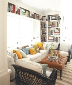 Small living room with ottoman and bookshelves. ... I love the book shelf going across the top of the window as well.