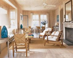 Architect Alan Wanzenberg created a sense of rustic elegance at his oceanfront retreat in Water Island, New York, with vintage woven-raffia armchairs by Charlotte Perriand and Dominique wood chairs with canvas cushions; the walls and ceiling are sheathed in whitewashed cedar.