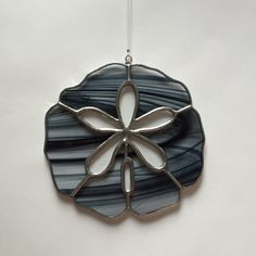 This beautiful stained glass sand dollar suncatcher is made from hand cut glass. The pieces are individually wrapped in copper foil, and soldered. It comes ready to hang with clear line, and measures approximately 4 1/4 inches in diameter (each sand dollar varies slightly). This suncatcher will look great in any window. Colors: black and clear & clear baroque glass.  This item is made from real glass and will not fade. Stained glass suncatchers make a great gift for yourself or a lov...