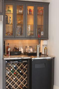 Custom wine rack in bar area with Kegerator and glass door liquor cabinets.