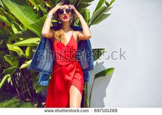 Fashion outdoor portrait of stunning blonde woman, wearing luxury elegant evening dress,  earnings sunglasses. and hipster jacket, tropical leaves on background.