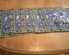 """This is a lovely vintage set of 6 Williamsburg blue daisy cotton place mats. The center of the place mats have a large blue daisy pattern made of various blue and purple shades. There is a blue and green border design that runs on the edge of the place mats. These place mats are one sided. These place mats appear to have been barely used.  Measures: 19.5"""" x 14.10""""."""