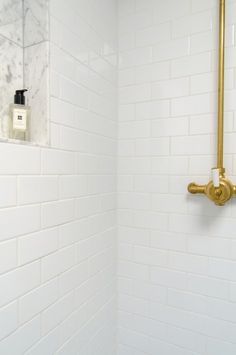 white subway tile with brass fixtures and marble inset shelf