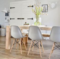Comedor estilo nórdico con sillas Eames blancas.