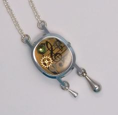 Handmade music themed Steampunk watch case pendant. Music sheet background, vintage watch parts and a pale green faceted glass crystal were trapped in layers of resin set in a silver tone watch case. With repurposed silver drop dangles, strung on a silver tone chain. Signed and dated (2012) on ba...