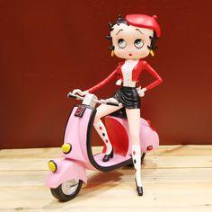 No se puede tener más estilo que nuestra Betty, desde luego está impresionante encima de su Scooter rosa con ese aire vintage. En esta figura está en una pose super sexy con un look parisino muy chic. Esta figura está entre dos mundos que casan a la perfección y de los cuales no podrás resistirte: las Scooters y Betty Boop. En esta ocasión la figura de resina mide 30 centímetros de ancho por 30 centímetros de alto.
