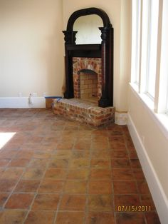 The antiqued terra cotta tile in this room draws much attention to itself while blending well with the varied red brick fireplace. The added rub that comes varied throughout the rub adds a depth of color that help to bring the dark wood and flooring together