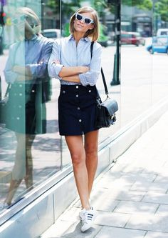 A blue button-down blouse is worn with a button-down skirt, adidas sneakers, a black crossbody bag, and cat-eye sunglasses