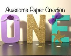 Mermaid inspired paper mache one letters great for your little one first birthday party,photo props,birthday decor. Hand glitter hand painted.  Please read........Letters are paper mache letters not wood. 8inches tall O letter.......hand glitter sealed to prevent glitter from falling. N letter... purple paint. Each circle hand glued on one by one. Materials for circles quality cardstock paper E letter....hand glitter with purple glitter and sealed to prevent glitter from falling. Gems hand gl...