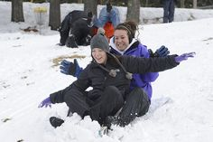 Students enjoy sledding down the hill above the practice soccer field.