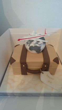 A travelling themed cake complete with cake suitcase and globe and plane flying around the world.  By Sarahs Cakes by Design.