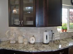 Ice Brown also called Alaska White Granite countertops with dark brown cabinets and a light subway tile backsplash. @GlobalGranite