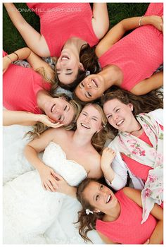 Bridal party wedding day photograph. All girls lying on the skirts of the wedding dress. Southend Barns wedding venue in Chichester, West Sussex. Smiling happy faces. Coral shift dresses, white sweetheart neckline, corseted wedding dress. Trending, current Wedding portrait photography ideas.