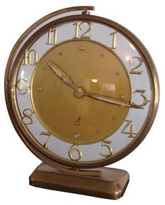 """A fine French art deco table clock by the Compagnie Industrielle de Macanique Horelogere which used the trademark """"JAZ"""" from 1919 to 1941. This clock is from a line of deco clocks that the company introduced in 1934. The circular brass clock frame encloses the floating numerals around a gold ground. The clock body swivels horozontically."""