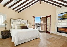 mediterranean-master-bedroom-with-fireplace-and-arched-ceiling-and-outdoor-balcony-views