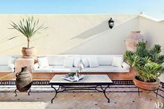 Bright white cushions line the built-in benches of a Morocco home's sun-splashed terrace. - Photo: Simon Watson