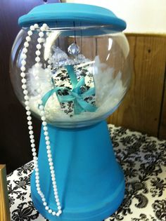 """I got a fish bowl and a plant pot, filled it with fake pearls, crystals and feathers as a large center piece for the """"breakfast at Tiffany's"""" party"""