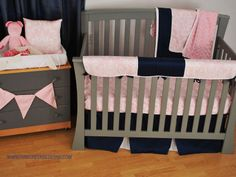 Navy and light pink toddler bedding with a crib rail teething guard with pink damask fabric